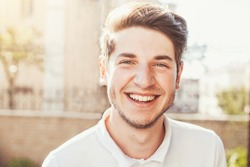Handsome man outdoors portrait. Man smiling, looking in the camera
