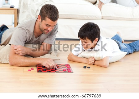 Handsome man playing checkers with his son lying on the floor at home