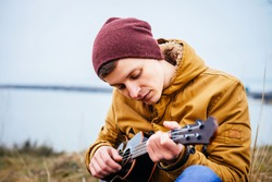 Handsome man playing classic guitar sitting on the beach in vacations