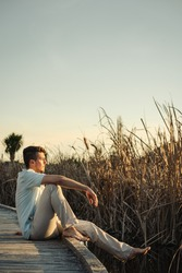 Handsome man posing in profile on bare feet sitting on wooden walkway on lake shore. Vertical portrait photography