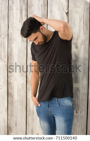 Handsome man posing with hands in pocket against wooden background #711500140