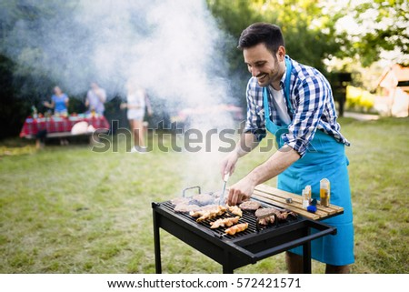 Handsome man preparing barbecue for friends outdoor