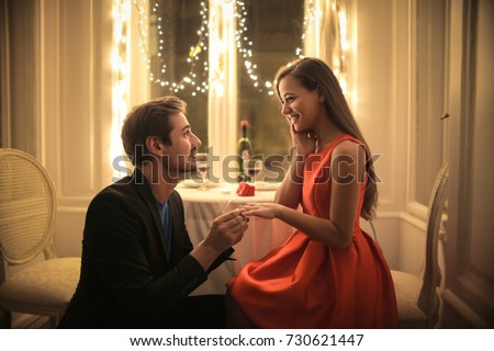 Handsome man proposing a beautiful woman to marry him in an elegant restaurant #730621447