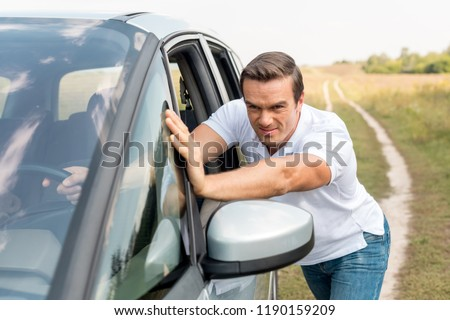 handsome man pushing his broken car in field