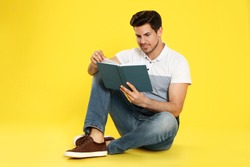 Handsome man reading book on color background, space for text
