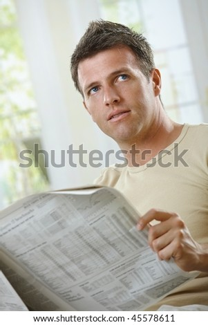 Handsome man reading newspaper at home in casual wear.