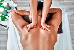 Handsome man relaxing and enjoying a deep tissue back massage at the spa salon. Top view