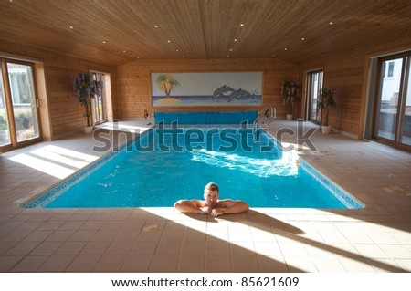 Handsome man relaxing in a indoor swimming pool - stock photo