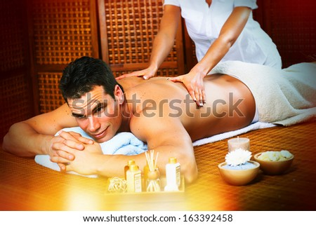 Handsome man relaxing in spa massage salon