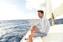 Handsome man relaxing on saiboat in middle of the sea