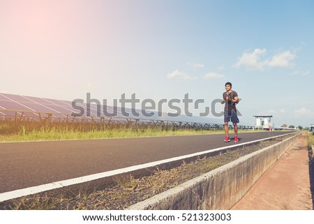 handsome man running on road with solar power plant in morning ;Healthy lifestyle with green energy #521323003
