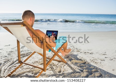 Handsome man scrolling on his tablet pc on the beach