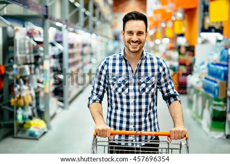 Handsome man shopping in supermarket pushing trolley
