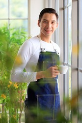 Handsome man short black hair wearing t-shirt jean apron holding coffee cup dimple smiling standing looking at camera. Photo blur selective focus his warm face. Indoor with sunlight and air filtering.