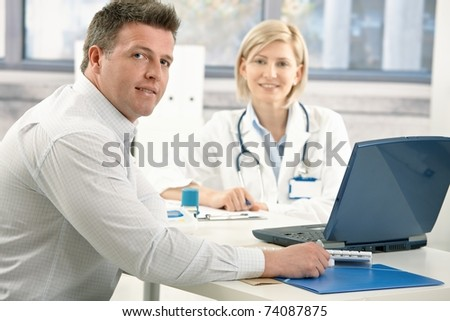 Handsome man sitting in doctor's office, smiling, on appointment with medical expert.?