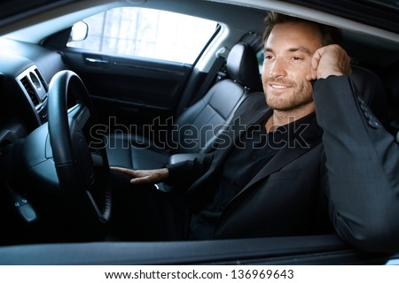 Handsome man sitting in limousine, talking on cellphone, smiling.