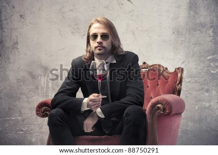 Handsome man sitting on an armchair and holding a glass of wine