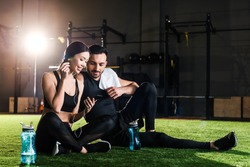 handsome man sitting on grass and looking at smartphone in hands of beautiful woman