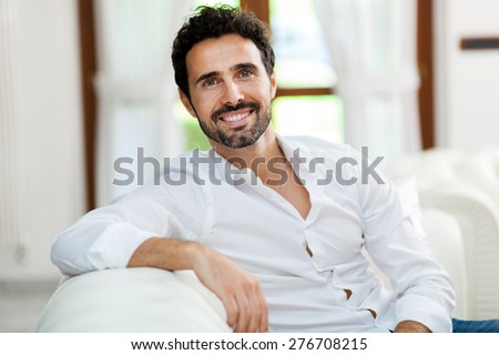 Handsome man sitting on his sofa