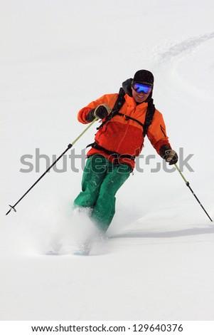Handsome man skiing fresh powder snow.
