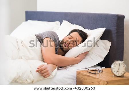 Handsome man sleeping in his bedroom. Man sleeping with alarm clock in foreground. Serene latin man sleeping peacefully.