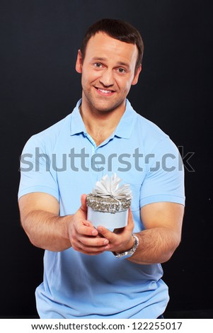 Handsome man smiling and holding a gift over a black background