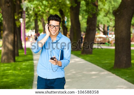 handsome man smiling and listening to music in the park - stock photo