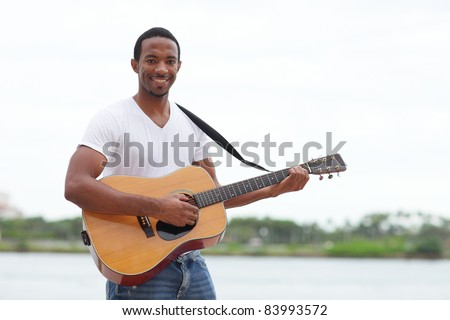 Handsome man smiling and playing a guitar