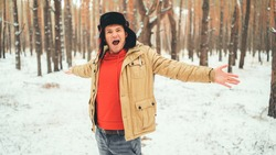 Handsome man standing and singing in forest in winter season. Young male wearing beige jacket over red hoodie and earflap hat with his arms outstretched sings in snowy forest.