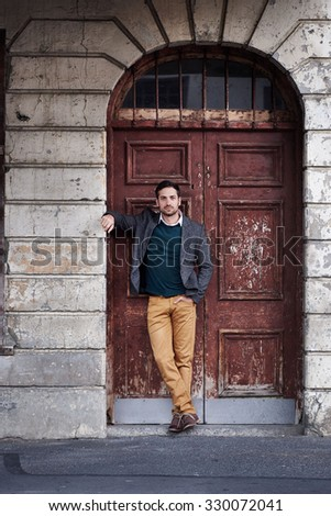 Handsome man standing casually in the doorway of a vintage building in an urban environment