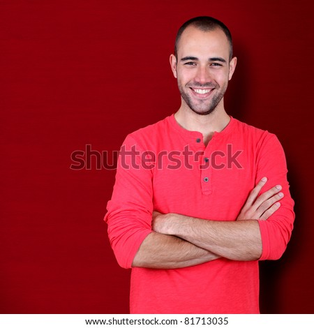 Handsome man standing on red background