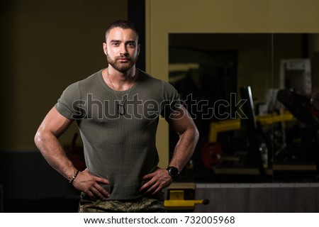 Handsome Man Standing Strong In Green T-shirt And Army Pants Flexing Muscles - Muscular Athletic Bodybuilder Fitness Model Posing After Exercises