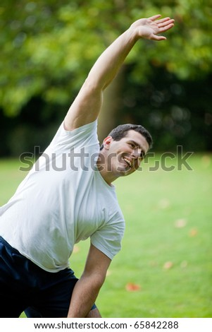 Handsome man stretching at the park - fitness concepts - stock photo