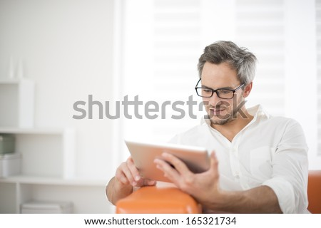 handsome man surfing on tablet on a couch #165321734