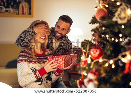 Handsome man surprising a girl with a Christmas present.