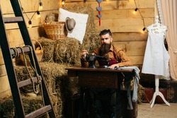 Handsome man tailor or dressmaker with beard and moustache sews clothes on vintage sewing machine in rustic workshop