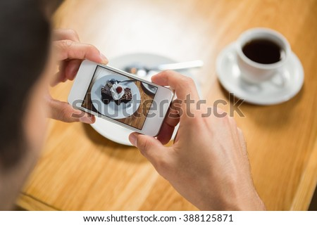 Handsome man taking a picture of his food in a pub