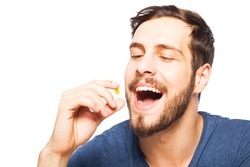 handsome man taking pills, isolated in white