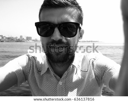 Handsome Man Taking Selfie.Close up portrait of man,man in sunglasses,stylish outfit,shirt,bearded man,man on the sea,relax,attractive,spring vacations,casual wear,happy face,pretty haircut,travel