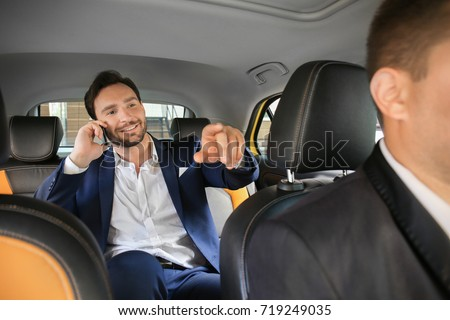 Handsome man talking on phone while sitting in taxi car