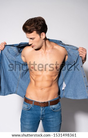 handsome man touching denim shirt while undressing on white