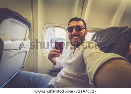 handsome man travel take photo selfie inside airplane - Cheerful tourist taking self photo with mobile phone into airplane - Concept of happiness and holidays