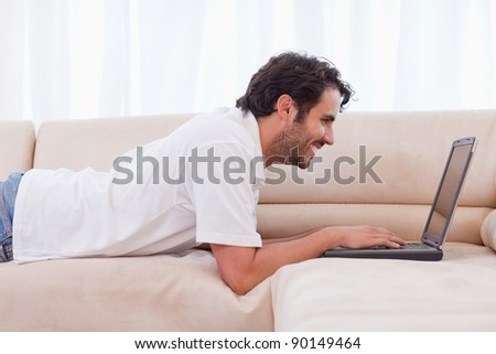 Handsome man using a notebook in his living room
