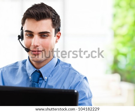 Handsome man using an headset in front of a computer monitor