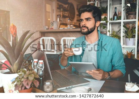 Handsome man using digital tablet and laptop while sitting indoors. Freelance work. Place of work. New business. - Stock Image #1427872640