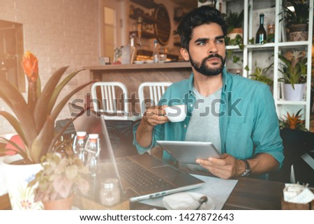 Handsome man using digital tablet and laptop while sitting indoors. Freelance work. Place of work. New business. - Stock Image #1427872643