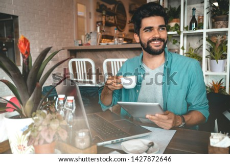 Handsome man using digital tablet and laptop while sitting indoors. Freelance work. Place of work. New business. - Stock Image #1427872646