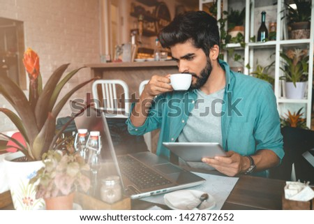 Handsome man using digital tablet and laptop while sitting indoors. Freelance work. Place of work. New business. - Stock Image #1427872652