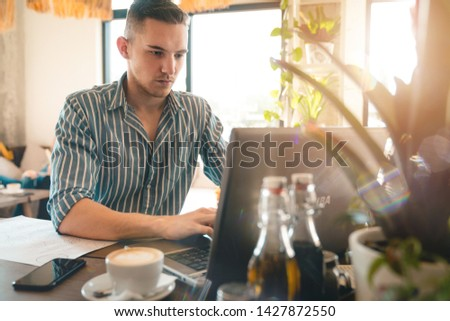 Handsome man using laptop while sitting indoors. Freelance work. place of work. New business. - Stock Image #1427872550