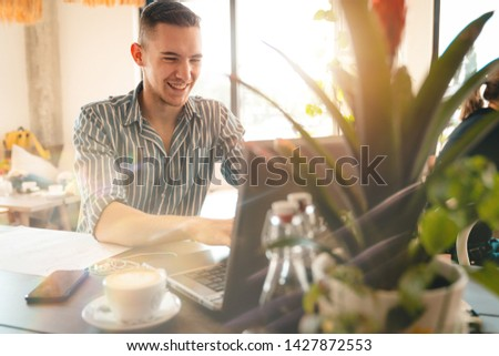 Handsome man using laptop while sitting indoors. Freelance work. place of work. New business. - Stock Image #1427872553